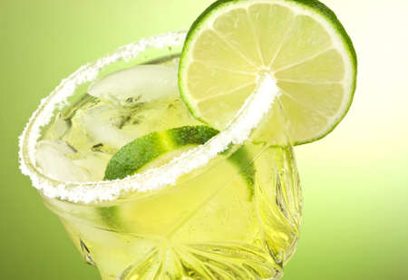 Refreshing summer cocktail drink with limes and ice isolated on green gradient background with copy space