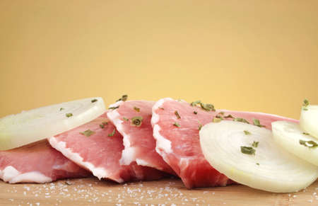 loin chops: Juicy raw pork loin chops with onion slices and spices on wooden cutting board with copy space  Stock Photo