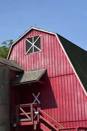old red barn: Bright red barn on rural farm against bright blue sky. Stock Photo