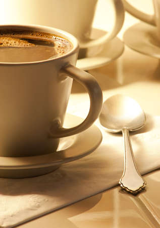 Cup of hot black espresso coffee with spoon and cups in background