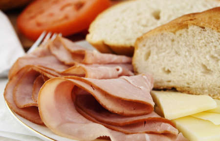 Delicious lunch time spread with ham, bread, cheese and tomatoes with silver fork
