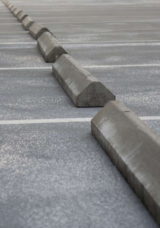 Concrete grey parking stoppers diagonal on empty parking lot. photo