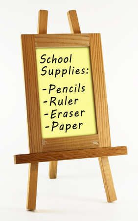 back to school supplies: List of back to school supplies in wooden frame on easel isolated on white background. Stock Photo