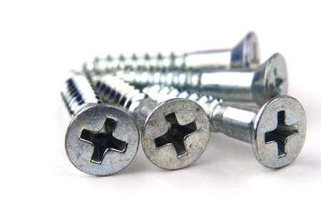 Close up macro of silver hardware screws isolated on white background with copy space. photo