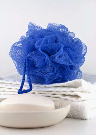 Blue bath puff with clean white towel and soap in dish on white background