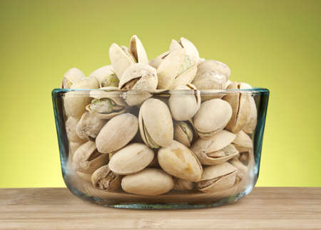 Delicious cracked pistachio nuts in glass bowl against green background.