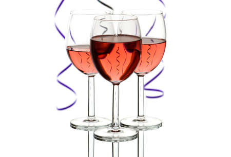 Three wine glasses with rose wine and party streamers isolated on white background with copy space