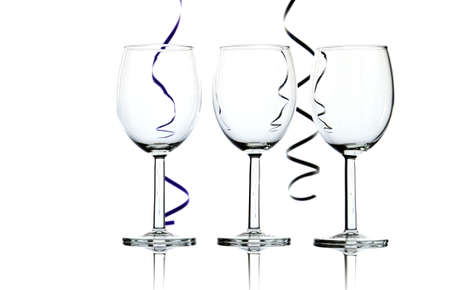 Three empty wine glasses and party streamers backlit against white background - abstract