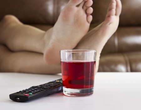 Persons feet up on coffee table while watching TV with remote control and drink on table.