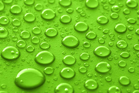Shiny water drops sprayed on textured green surface. Stock Photo