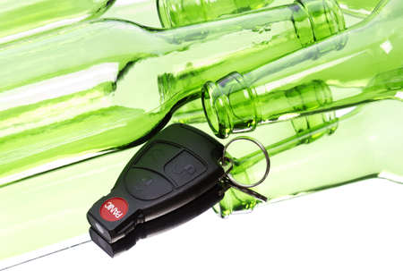 intoxicated: Car key and bunch of empty glass beer bottles to illustrate drunk driving concept. Stock Photo