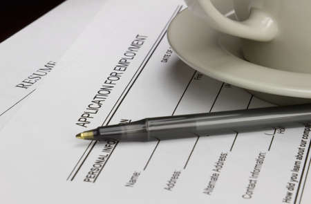 Blank employment application with resume, pen and coffee on desk. photo