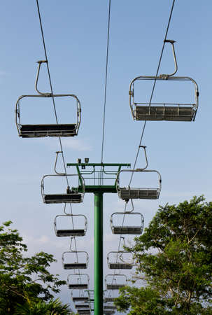 chair lift: Fun chair lift sky ride with blue sky and foliage in background. Stock Photo
