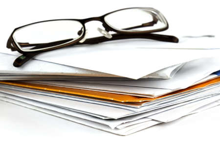 Stack of postal mail with pair of eyeglasses on white background. photo