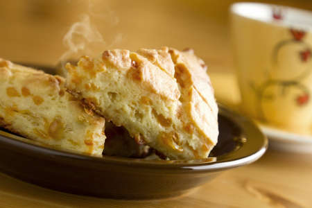 Delicious hot baked cheese biscuits on plate with cup of coffee  photo