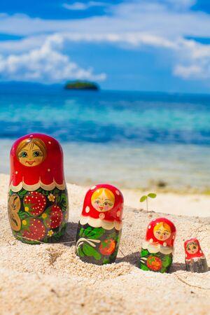 matriosca: Photo Rows Puzzle Russian Dolls Matrioshka Souvenir Untouched Tropical Beach in Bali Island. Vertical Picture. Blurred Background. Closeup Stock Photo