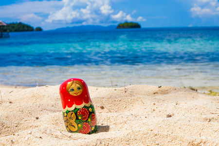 Photo Russian Handmade Dolls Matrioshka Untouched Tropical Beach in Bali Island. Horizontal Picture. Blurred Background. Closeup