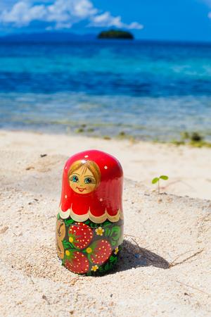 Photo Russian Dolls Matrioshka Souvenir Untouched Tropical Beach in Bali Island. Vertical Picture. Blurred Background. Closeup
