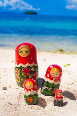 matriosca: Photo Rows Puzzle Russian Dolls Matrioshka Family Souvenir Untouched Tropical Beach in Bali Island. Vertical Picture. Blurred Background. Closeup