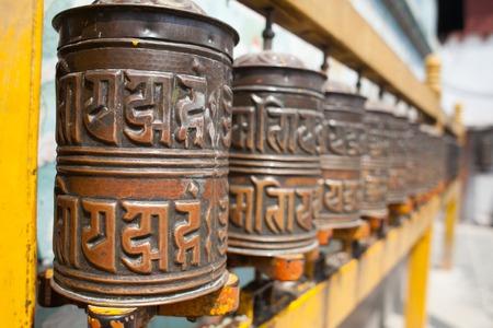 devote: Tibetan prayer wheels or prayers rolls of the faithful Buddhists. Horizontal. Closeup photo Stock Photo