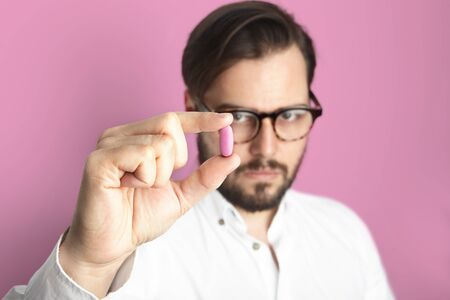 Young Bearded Man Wearing White Shirt Glasses Holding Hand Pink Color Pill.Medicine Health Care People Concept Photo.Adult Serious Doctor Rose Empty Background.Horizontal