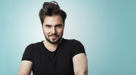 Portrait Handsome Bearded Man Wearing Black Color Tshirt.Beauty Lifestyle People Concept Photo.Adult Smiling Hipster Guy Empty Gray Background.Horizontal Wide.Soft Shadows Effect Stock Photo