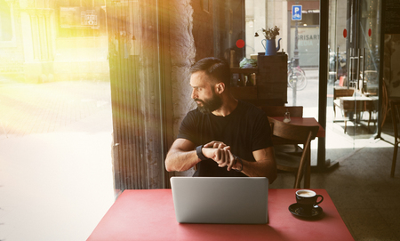 Young Bearded Businessman Wearing Black Tshirt Working Laptop Urban Cafe.Man Sitting Wood Table Cup Coffee Looking Through Window Touch Smartwatch.Coworking Process Business Startup Blurred Background Stock Photo