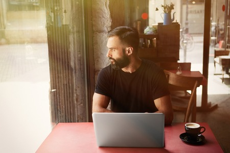 Young Bearded Businessman Wearing Black Tshirt Working Laptop Urban Cafe.Man Sitting Wood Table Cup Coffee Looking Through Window.Coworking Process Business Startup.Blurred Background.Sunlight effect Stock Photo