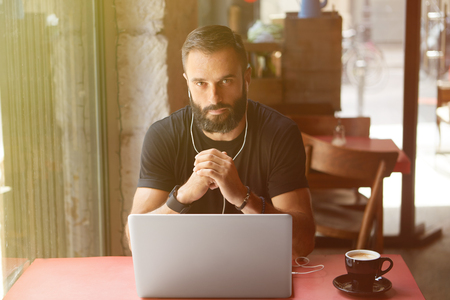 Young Bearded Businessman Wearing Black Tshirt Working Laptop Urban Cafe.Man Sitting Wood Table Cup Coffee Listening Music.Coworking Process Business Startup.Blurred Background.Sunlight effect