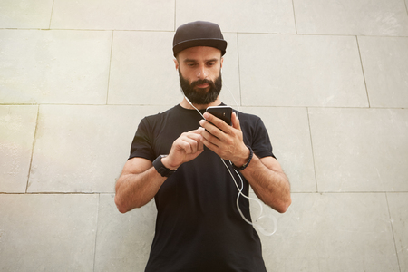 Bearded Muscular Man Wearing Black Tshirt Blank Snapback Cap Summer Time.Young Men Standing Opposite Empty Gray Concrete Wall Background Using Smartphone Headphones.Horizontal Mockup Stock Photo