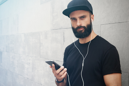 Bearded Muscular Man Wearing Black Tshirt Blank Snapback Cap Summer Time.Young Men Smiling Opposite Empty Gray Concrete Wall Background Using Smartphone Headphones.Horizontal Mockup.Side View
