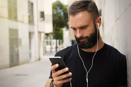 Bearded Muscular Man Wearing Black Tshirt Blank Snapback Cap Summer Time.Young Men Using Smartphone Headphones Looking Screen Smiling.Horizontal Stock Photo