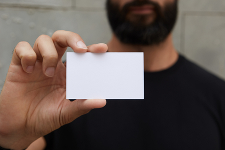 Bearded Man Wearing Casual Black Tshirt Showing Blank White Business Card.Blurred Background Ready Corporate Private Information.Horizontal Mockup Stock Photo