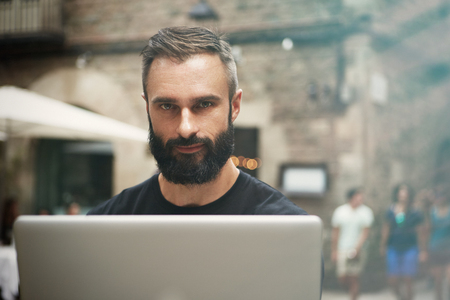 Closeup Portrait Handsome Bearded Businessman Wearing Black Tshirt Working Laptop Urban Cafe.Young Manager Work Notebook Outdoor Place.Coworking Process Business Startup.Blurred Background