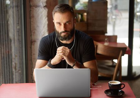 Handsome Young Bearded Businessman Wearing Black Tshirt Working Laptop Urban Cafe.Man Sitting Wood Table Cup Coffee Listening Music.Coworking Process Business Startup.Blurred Background Stock Photo