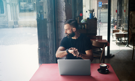 Young Bearded Businessman Wearing Black Tshirt Working Laptop Urban Cafe.Man Sitting Wood Table Cup Coffee Looking Through Window Touch Smartwatch.Coworking Process Business Startup.Color Filter Stock Photo