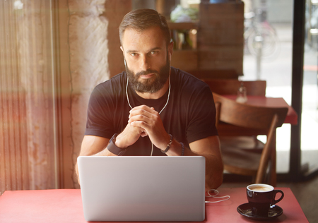 Young Bearded Businessman Wearing Black Tshirt Working Laptop Urban Cafe.Man Sitting Wood Table Cup Coffee Listening Music.Coworking Process Business Startup.Blurred Background.Sunlight Color Effect