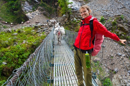Portrait Young Pretty Girl Wearing Red Jacket Trail Mountains.Mountain Trekking Landscape.Caravan Animal Donkeys Loaded Bags View Background.Woman Happy Smiling Cable Bridge.Horizontal Photo