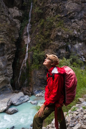 Portrait Young Pretty Girl Wearing Red Jacket Backpack Trail Mountains.Mountain Trekking Landscape WaterFall View Background.Woman Happy Smiling Close Rock River.Horizontal Photo