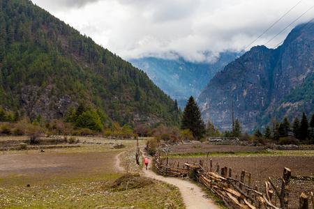 sherpa: Nepalese Sherpa Hiking Mountain Trail Village.Old Man Walking Loaded Bags Track Traveler Beautiful Noth Asia.Himalaya Summer Valley Landscape Background.Horizontal Photo