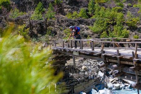 Landscape Fast Mountains River Hiking Himalayas.Beautiful View Wood Bridge End Summer Season Background.Green Threes Cloudy Blue Sky Mountainous Rocks.Man Travelers Backpacker Image.Horizontal Photo