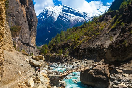 Landscape Fast Mountains River Hiking Himalayas.Beautiful View Wood Bridge End Summer Season Background.Green Threes Cloudy Blue Sky Mountainous Rocks.Travelers Backpacker Image.Horizontal Photo