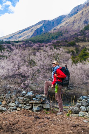 Young Pretty Woman Wearing Red Jacket Backpack Trail Mountains.Mountain Trekking Rocks Path Landscape View Background. Girl Happy Smiling Close Rock.Vertical Photo