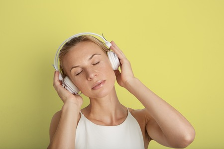 Portrait Handsome Young Woman Listening Headphones Music Player Blank Yellow Color Background.Pretty Girl Enjoy Audio Smiling Hands Up.Beauty Lifestyle Fashion Hipster People Abstract Concept Stock Photo