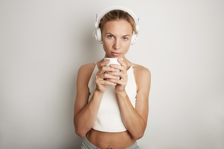 Portrait Handsome Young Woman Listening Music Player Headphones Blank White Background.Pretty Girl looking Holding Coffe Cup Hands Empty Wall.Beauty Lifestyle Fashion Hipster People Abstract Concept
