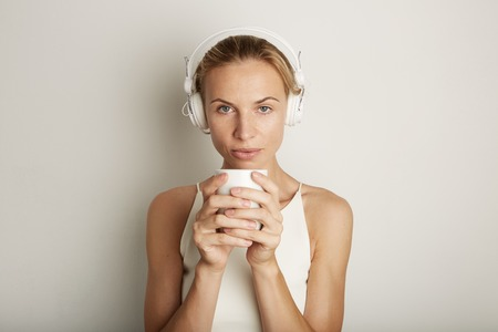 Portrait Handsome Young Woman Listening Music Player Headphones Blank White Background.Pretty Girl looking Holding Coffe Cup Hands Empty Wall.Beauty Lifestyle Fashion Hipster People Concept.Closeup