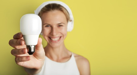 Portrait Handsome Young Woman Listening Music Player Headphones Blank Yellow Background.Pretty Girl Smiling Holding Energy Safe Bulb Hand Empty Wall.Beauty Lifestyle Fashion Hipster People.Wide Space Stock Photo