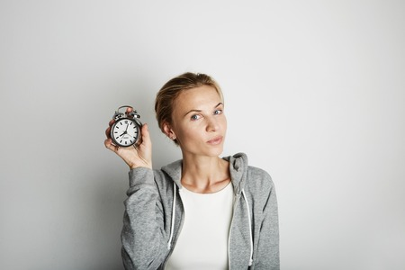 Portrait Handsome Young Woman Posing Blank White Background.Pretty Girl Smiling Holding Vintage Alarm Clock Hand Empty Wall.Beauty Lifestyle Fashion Hipster People.Casual Time Abstract Concept
