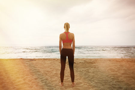 Young Sexy Girl Making Sport Workout Empty Sand Beach.Fitness Woman Spending Active Training Session Time Outdoor Sea. Summer Season Ocean.Horizontal Photo Cloudy Sky. Blurred background. Back View Stock Photo