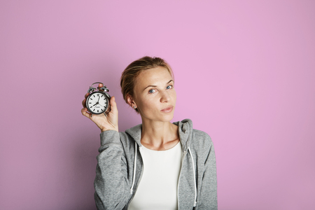 Portrait Handsome Young Woman Posing Blank Pink Background.Pretty Girl Smiling Holding Vintage Alarm Clock Hand Empty Wall.Beauty Lifestyle Fashion Hipster People.Casual Time Abstract Concept